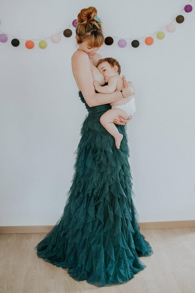allaitement petite fille 1 an, robe verte, guirlande colorée