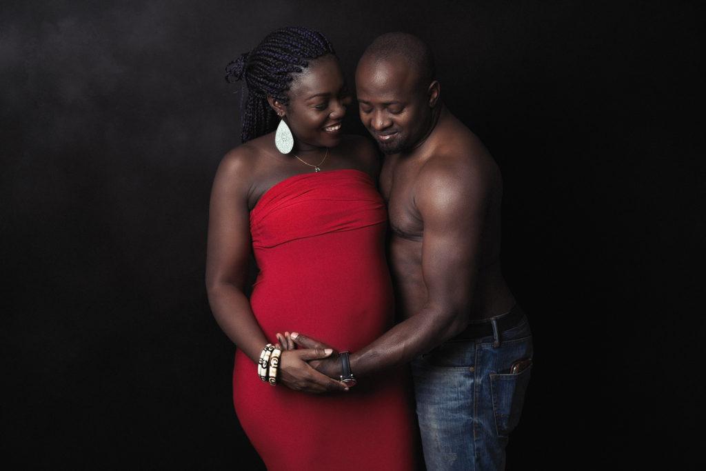 couple sur fond noir, femme enceinte. futurs parents. Photographie en studio aux Brenets, Neuchâtel
